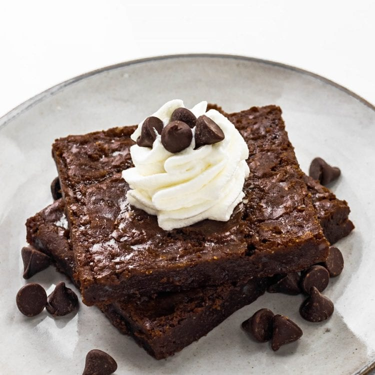 Almond Flour Brownies on a Plate with Whipped Cream and Chocolate Chips